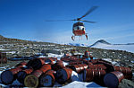 helicopter transports empty oilbarrels out of Antarctica