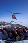 helicopter takes empty oilbarrels in antarctica