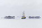 fishing boat and april snow on mounds of island Langeness