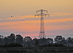 high-voltage transmission mast in red morning