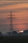 high-voltage transmission mast at sunrise