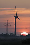 high-voltage transmission mast and windmill at sunrise