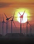 high-voltage transmission line and windmills at sunrise