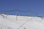 Stromleitung wirft Schatten im Schnee