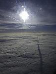 Schatten eines Kondesstreifens auf Wolken
