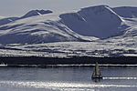 sailing boat and snowy mountains