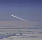 airplane with condensation trail above clouds