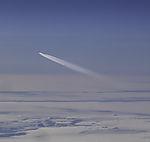 Flieger mit Kondensstreifen über den Wolken